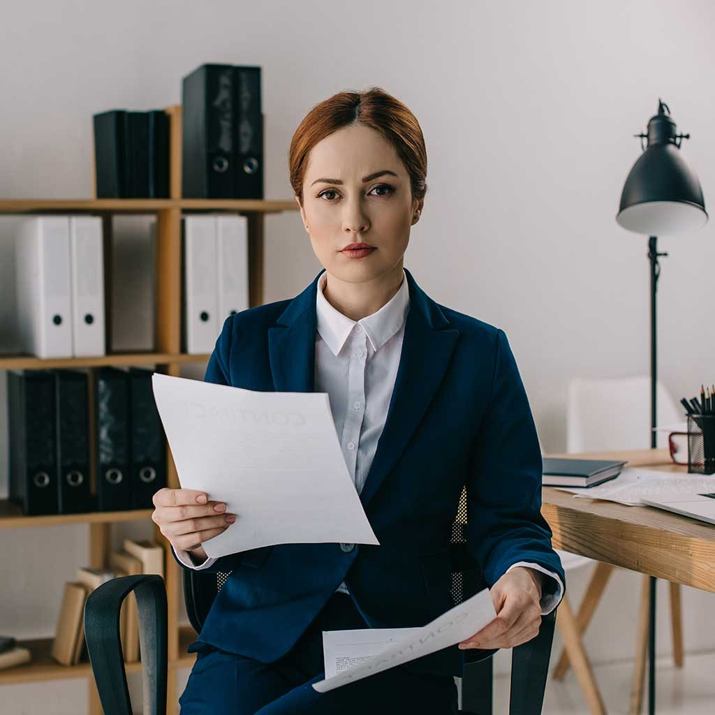 portrait-of-female-lawyer-in-suit-with-documents-i-AGD8X3M